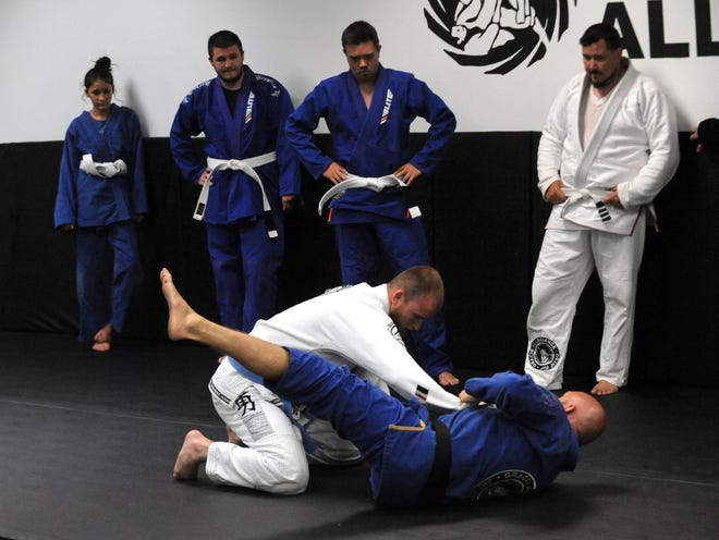 Doug Patton (in white) works with instructor Jason Cable during the adult class of the Gracie Allegiance Jiu-Jitsu Academy at Colony Square Mall. There are classes for youth and adults available.