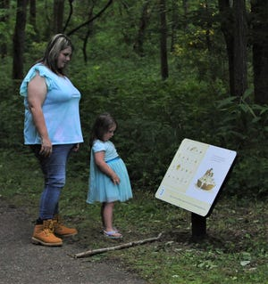 Shantae Snodgrass and her daughter, Gracelynn McConnell, read one of the panels along the Storybook Trail at Dillon State Park.