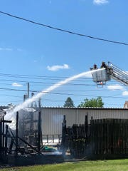 Firefighters from multiple departments watch as a New Concord ladder truck dumps gallons of water onto the remains of a storage building at Orme Hardware on Main Street that was destroyed by fire Friday afternoon.