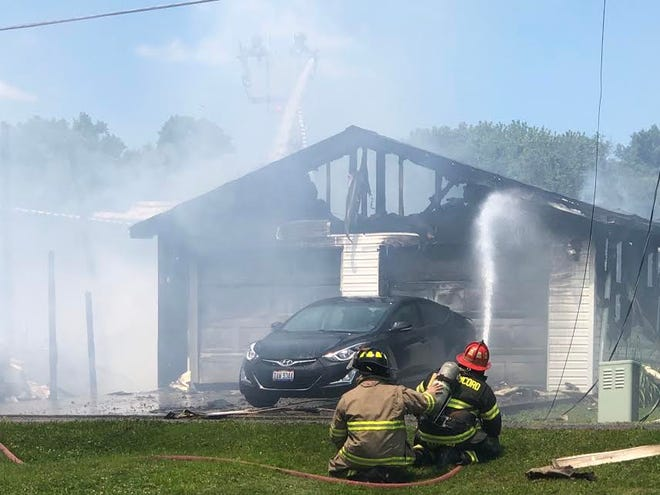 Firefighters from the New Concord Fire Department pour water onto the remains of a storage building and garage destroyed by fire Friday afternoon. The storage building was owned by Orme Hardware.