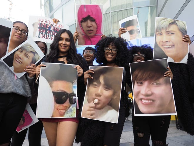 BTS fans pose with photos of their idols outside of the 2017 American Music Awards on November 19, 2017 in Los Angeles.