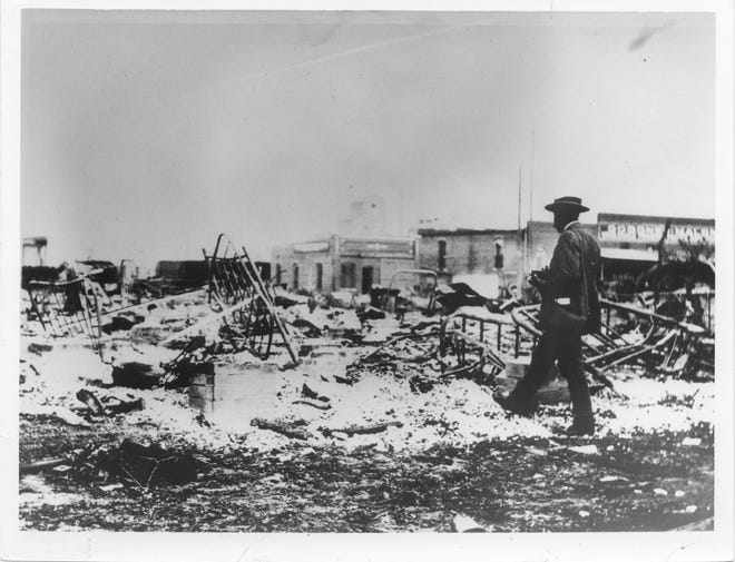 An African-American photographer  looking at the ruins of the Midway Hotel. The Goodner-Malone Co. is in the background.