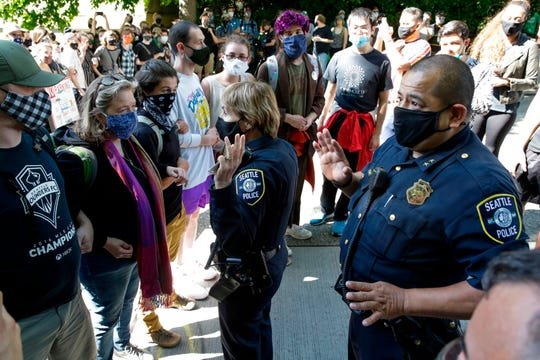 Deanna Nollette, Seattle's deputy chief of police and Adrian Diaz, deputy chief of police, are prevented by protesters from entering the newly created Capitol Hill Autonomous Zone (CHAZ) in Seattle on June 11, 2020.