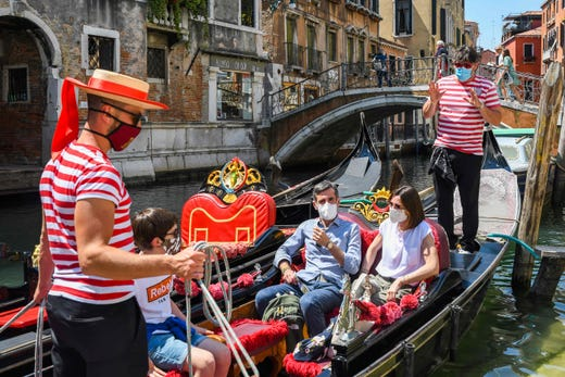 Gondoliers go with customers for a gondola ride on a canal in Venice, Italy on June 12, 2020 as the country eases its lockdown aimed at curbing the spread of the COVID-19 infection, caused by the novel coronavirus.