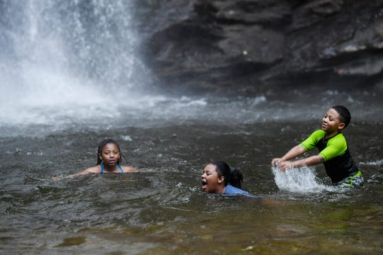 From left, siblings Makayla, 11, Aniyah, 9, and Josiah McDowell, 8, of Forest City, splash and cool off in the water below Looking Glass Falls in the Pisgah National Forest in Brevard June 12, 2020. It was their first time visiting.