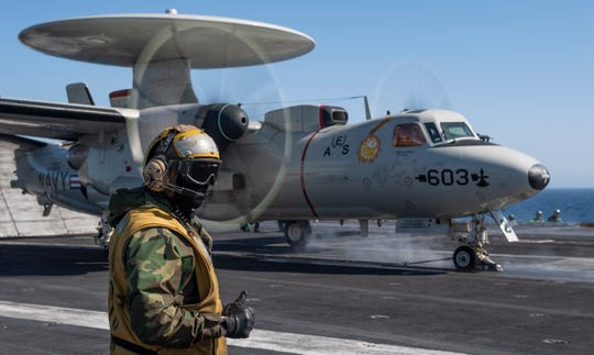 "A sailor directs an E-2C Hawkeye, from the ""Sun Kings"" of Carrier Airborne Early Warning Squadron (VAW) 116, on the flight deck aboard the aircraft carrier USS Nimitz (CVN 68). The E-2C Hawkeye was the first aircraft to launch on Nimitz's 2020 deployment. Nimitz, the flagship of Carrier Strike Group 11, is deployed conducting maritime security operations and theater security cooperation efforts."