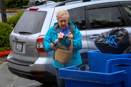 Claudia McDonald tosses a basket and other items she no longer wants into bins at Goodwill in Silverdale. She said items have been collecting in her home over time, but she wasn't able to donate recently because of COVID-19 closures.