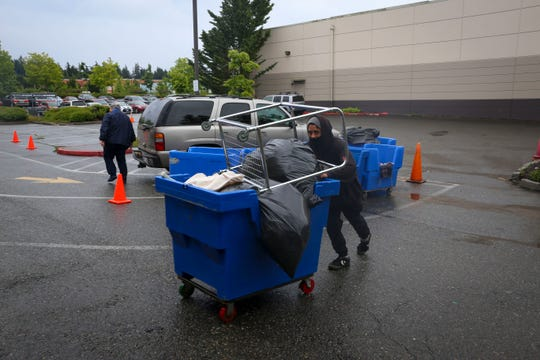 A Silverdale Goodwill employee pushes a cart full of donated items back into the store to be sorted on Friday.