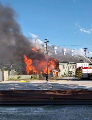 Fire rages through the vacant Norfolk Southern Railway diesel locomotive shops Wednesday evening in Ludlow. Police said they will charge two juveniles with arson in connection with the fire at the railroad building and a fire in an Elm Street house that firefighters had to fight simultaneously.
