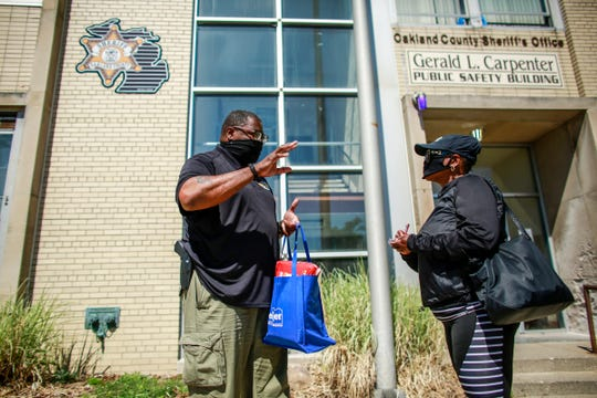 Oakland County Sheriff Deputy Gill Garrett, 45, of Pontiac talks with Tracy Coleman in front of the Oakland County Sheriff's substation in Pontiac where he works community policing, photographed on Friday, June 12, 2020.