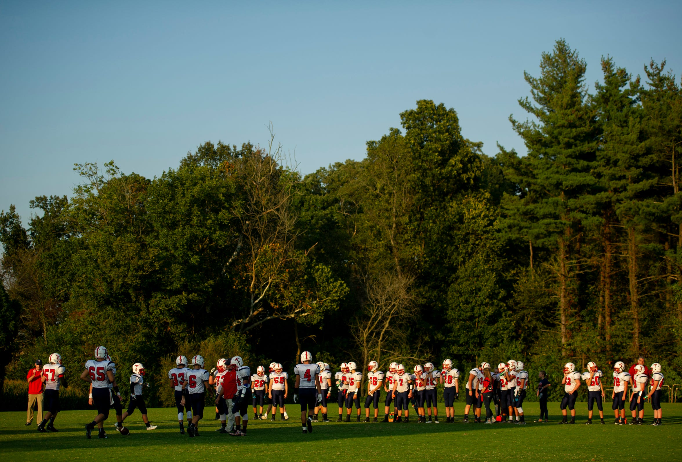 The Tecumseh High School football team lines up in a field downhill from the Forest Park High School football field before playing Forest Park in Ferdinand, Ind., Friday evening, Sept. 13, 2019.