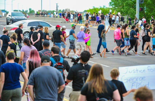 Black Lives Matter protesters make their way across River Drive to the Central Avenue West Bridge on Friday, June 12, 2020.