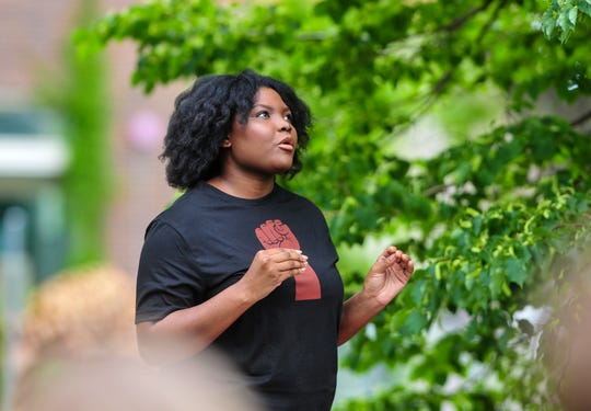 Cedrianna Brownwell the organizer of Friday's Black Lives Matter protest opens by welcoming attendees and stating their goals, which includes: ending qualified immunity for police, requiring police to take de-escalation training, and defunding the police, which involves reallocating funds to support social programs.