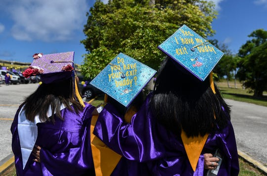 Graduating students show off their decorated caps while waiting for the George Washington High School graduation ceremony to begin in Mangilao, June 13, 2020.