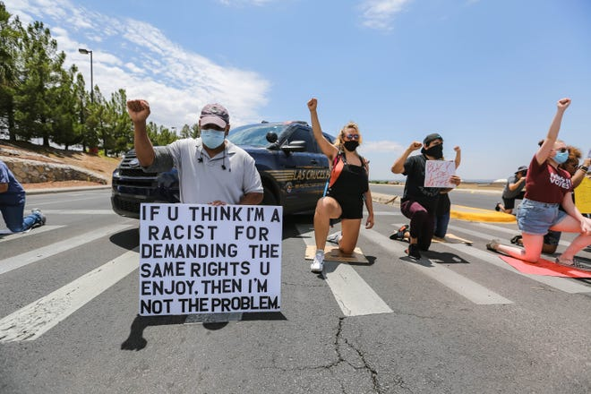 Demonstrators take a knee to protest police brutality, blocking Telshor Blvd and Foothills Road near Hotel Encanto in Las Cruces on Saturday, June 13, 2020.