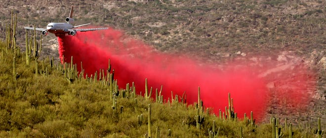 A DC-10 VLAT drops below the ridge line in his path to make a slurry drop as the battle moves to the northwest and crews work to keep the Bighorn Fire from spreading through Catalina State Park, Oro Valley, Ariz., June 11, 2020.