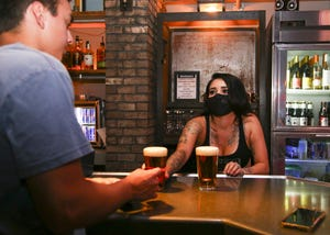 A bartender serves drinks wearing a face mask at Copper Blues on June 12, 2020. Live music returns to Phoenix with some venues encouraging social distancing and mask wearing.