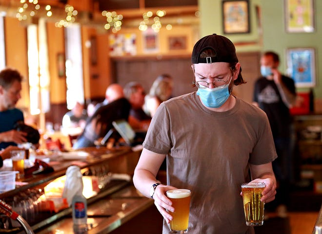 Bartender Ray Epley, of Holy Hound Taproom, serves customers at the restaurant/bar in York City, Friday, June 12, 2020. Friday would be day one for York County entering into the green phase of Gov. Wolf's plan to reopen Pennsylvania following nearly three months of restrictions placed to mitigate the spread of the coronavirus. Dawn J. Sagert photo