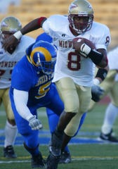 Midwestern State University quarterback Rahsaan Bell tries to escape Angelo State University linebacker Tyrell McCrea in a game Sept. 24, 2005.