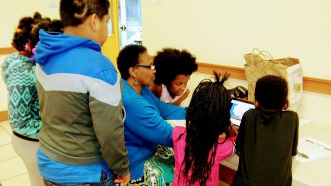 Sabrina Mack and students at the Delta Kappa Omega Providence Community Service Center before the coronavirus pandemic.