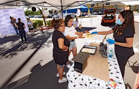 "Marketing and Special Events Manager, Kiley Arce, right, hands out gift cards during Tulare Outlets ""Gift a Grad"" program Friday, June 12, 2020. High school seniors could register online until May 29. After that community members chose seniors and gifted them a Tulare Outlets gift card."