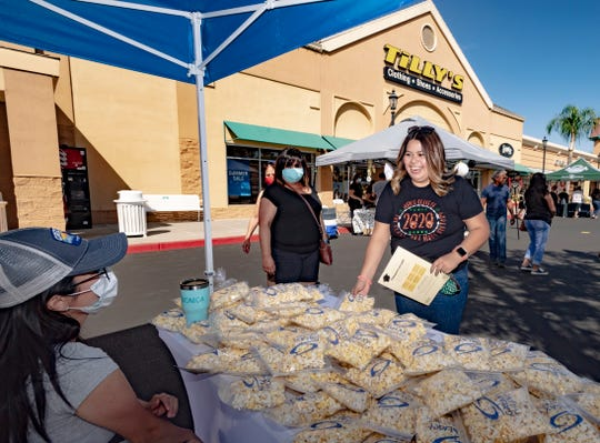 "Porterville High School graduate Briana Facio grabs a bag of popcorn along with her Tulare Outlets gift card and other promotional items Friday, June 12, 2020. High school seniors could register for the online ""Gift a Grad"" program until May 29. After that community members chose seniors and gifted them a Tulare Outlets gift card."