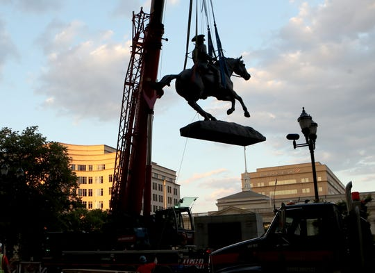 The statue of Caesar Rodney is hoisted from its pedestal on Rodney Square in Wilmington early Friday evening.