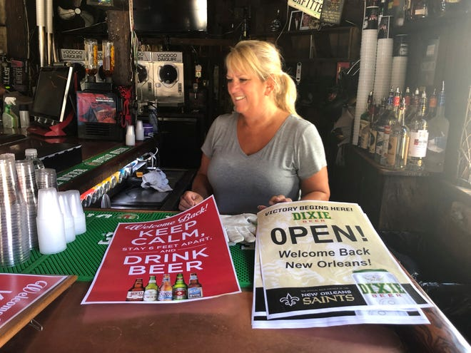 In this Friday, June 12, 2020 photo, Cherie Boos, manager of Lafitte's Blacksmith Shop Bar on Bourbon Street, stands behind the bar as workers prepare it for reopening. The city is allowing bars to open – with limited capacity and without live music – on Saturday. Bars were among the businesses shut down in mid-March as coronavirus infections increased in New Orleans and Louisiana became a hot spot for the disease.
