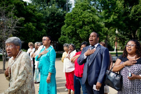 Participants sing the national anthem during a wreath-laying ceremony to commemorate Juneteenth at the Emancipation Memorial in Lincoln Park in the Capitol Hill neighborhood of Washington on June 15, 2012.