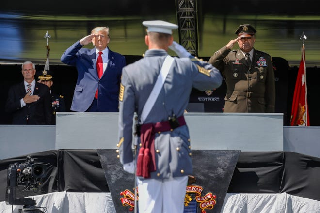President Donald Trump, left, and United States Military Academy superintendent Darryl A. Williams, right, salute alongside graduating cadets as the national anthem is played during commencement ceremonies on Saturday.