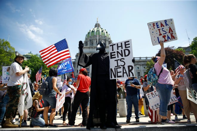 FILE - In this Friday, May 15, 2020 file photo, protesters hold a rally against Pennsylvania's coronavirus stay-at-home order at the state Capitol in Harrisburg, Pa. (AP Photo/Matt Rourke) ORG XMIT: NY595