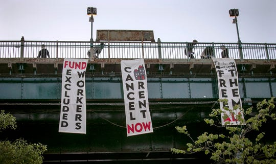 People from a support organization for immigrant and working-class communities unfold banners, including one advocating rent cancelation, on a subway platform in the Queens borough of New York during a vigil memorializing people who died from coronavirus.