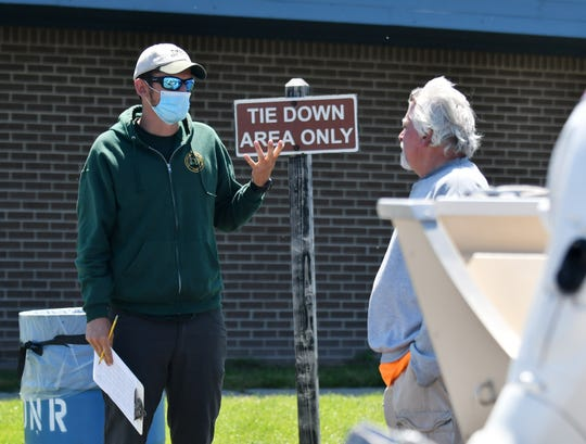 DNR fishing assistant Robbie Zambelli, 23, of Mt. Clemens talks with fisherman Rick Gunsch of Royal Oak, right, at the Harley Ensign Memorial boating access site in Harrison Township on June 14, 2020.