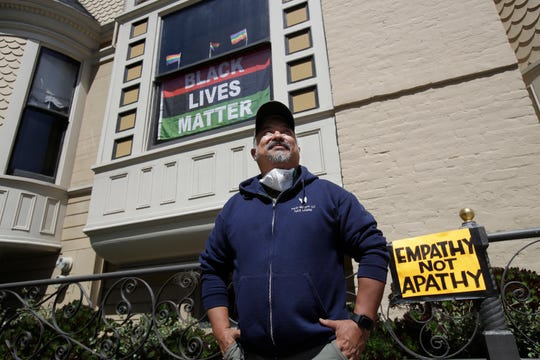 """James Juanillo poses outside of his home in San Francisco, Sunday. The CEO of a cosmetic company issued an apology Sunday after she and her husband confronted Juanillo and threatened to call police because he stenciled """"Black Lives Matter"""" in chalk on his San Francisco property, as the couple asserted that they know Juanillo doesn't live there and is, therefore, breaking the law."""