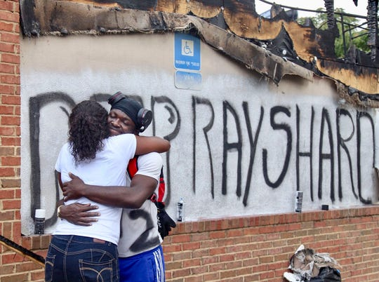 Eva Snow and Joseth Jett hug Sunday, June 14, 2020 after Jett spray painted over the top of graffiti from the night before and painted RIP Rayshard.