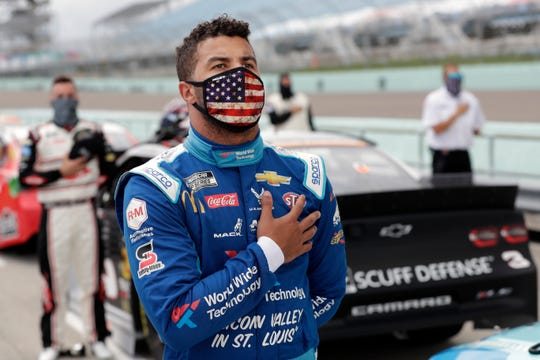 Bubba Wallace stands for the national anthem before a NASCAR Cup Series auto race Sunday in Homestead, Fla.