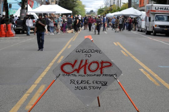 """A sign reads """"Welcome to CHOP,"""" Sunday inside what has been named the Capitol Hill Occupied Protest zone in Seattle. Protesters calling for police reform and other demands have taken over several blocks near downtown Seattle after officers withdrew from a police station in the area following violent confrontations. The CHOP name is a change from CHAZ (Capitol Hill Autonomous Zone) that was used earlier in the week."""