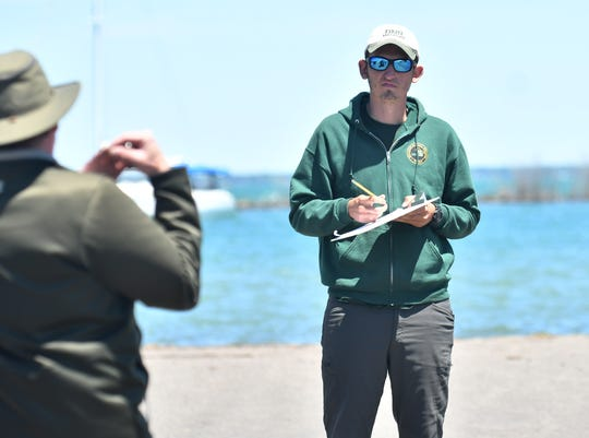 DNR fishing assistant Robbie Zambelli, 23, of Mount Clemens writes down information from fisherman Nick Garofalo of Clinton Township, left, at the Harley Ensign Memorial boating access site in Harrison Township on June 14, 2020.