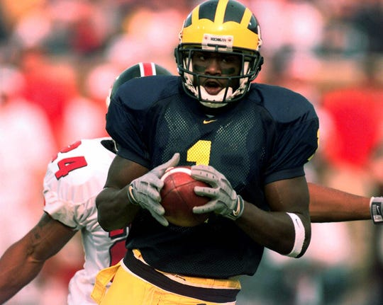 Michigan wide receiver David Terrell pulls in a 27-yard touchdown pass in front of Indiana cornerback Marcus Floyd at Michigan Stadium in Ann Arbor in 2000.