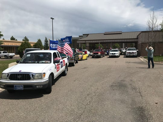 Vehicles line up in the drive-through of a former bank as they prepare to caravan through the city to celebrate the birthday of President Donald Trump.