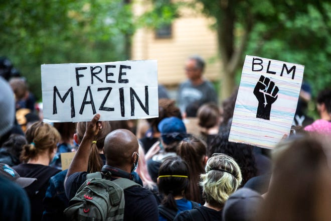 """People hold signs, """"Free Mazin"""" and """"BLM"""" during a protest organized by the Iowa Freedom Riders, Saturday, June 13, 2020, in Iowa City, Iowa. Mazin Mohamedali is an organizer in the Iowa Freedom Riders who was arrested."""