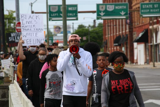Tim Jones, holding megaphone, leads protesters in a march from Founders Park to the Harding Memorial during the Black Lives Matter Rally 4 Justice on Saturday, June 13, 2020, in Marion.