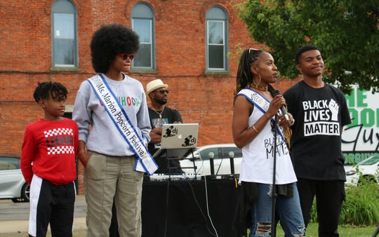 Candace Floyd, with microphone in hand, speaks to the crowd at the Black Lives Matter Rally 4 Justice on Saturday, June 13, 2020. Floyd talked about her concerns about raising her son, Caden Jones, 15, far right, in a society that is sometimes hostile to people of color. Jessica Coleman, second from right, read an essay about her son, Keelan, left during the rally.