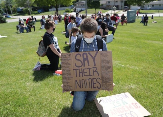 Waukesha protest march organizer Ben Strong on Sunday kneels for nine minutes outside the Waukesha Police Department, reflecting the time George Floyd was held down by a Minnesota police officer's knee, leading to Floyd's death. The group started its march downtown, walked to the Waukesha Police Department and returned to where it started.