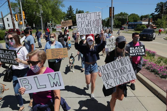 A group heads down Delafield Street during a march in protest of police brutality in Waukesha on Sunday.