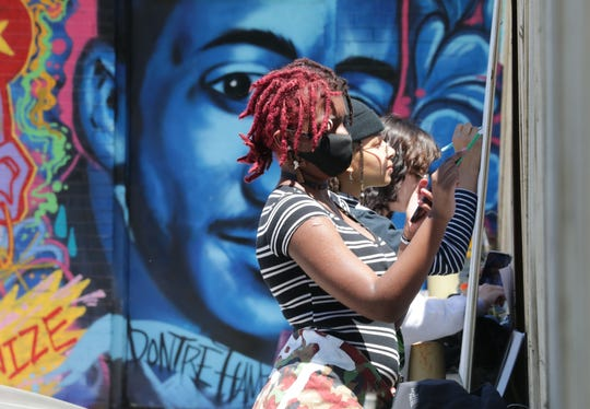 "Aminah Green, left, works with others on a collective mural for Black Lives Matter near the corner of East North Avenue and North Holton Street in Milwaukee on Sunday. The event, organized by the Muslims for Black Lives Mural group, Fanana Banana, involved people painting large panels to be attached to the fence with various Black Lives Matter messages and the words ""Our Kids Will Not Be Next,"" in response to to the death of George Floyd, who died after a Minneapolis police officer kneeled on his neck for more than eight minutes."