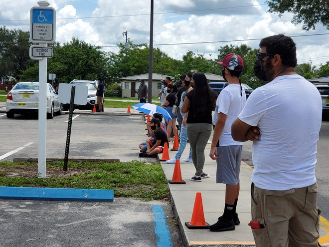 Sidewalks along Immokalee's Collier County Health Department building are full of people ready for a COVID-19 test Sunday.