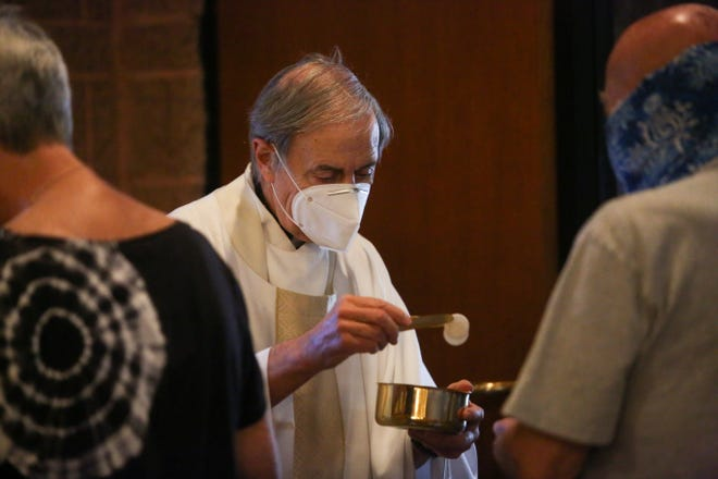 Rev. Monsignor Howard Lincoln offers communion to a parishioner at Sacred Heart Catholic Church in Palm Desert, Calif. on Sunday, June 14, 2020. Special cleaning measures and social distancing guidelines were implemented for the safety of parishioners.