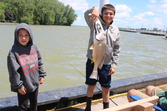 Jackson and Anthony Koloff, of Delaware, Ohio, show off what was around their twentieth catch during a fishing trip at downtown Port Clinton.