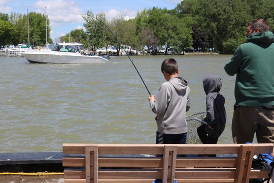 Anthony Koloff reels in a fish as his brother, Jackson, gets ready with a net during a trip to downtown Port Clinton on Saturday.